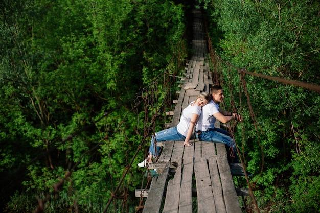 Casal emocional feliz abraçando na ponte de madeira