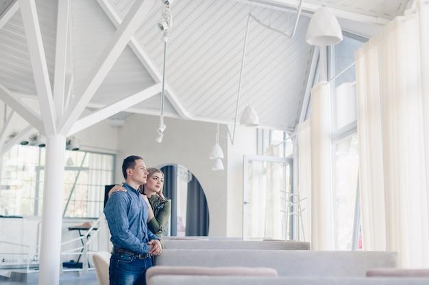 Casal emocional feliz amando um ao outro interior em um interior branco elegante
