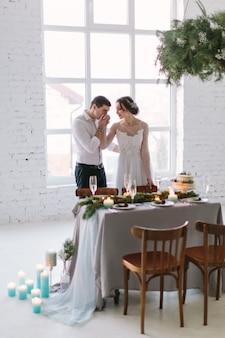 Casal emocional lindo recém-casado sorrindo, beijando e abraçando na recepção do casamento no salão branco com decorações de casamento