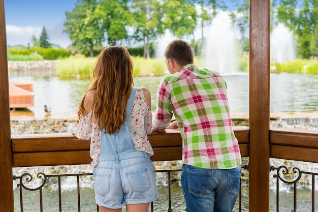 Casal encostado na grade do gazebo de madeira em frente a uma cachoeira artificial em um parque com lago, fonte e diferentes árvores