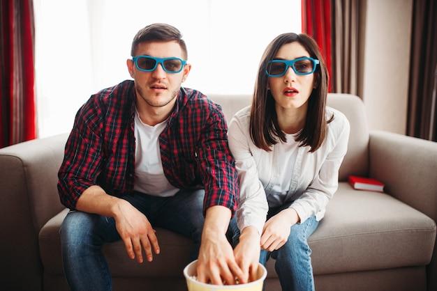 Casal enfeitiçado de óculos sentado no sofá, homem e mulher assistem tv e comem pipoca em casa
