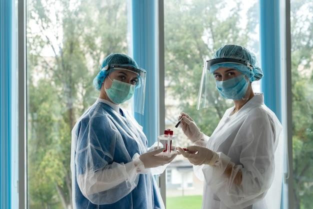 Casal enfermeira vestindo roupas de proteção médica segurando amostras de sangue em tubo de ensaio em clínica moderna