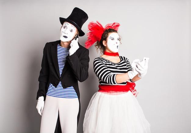 Casal engraçado de mímicos falando ao lado dos telefones. conceito de dia da mentira