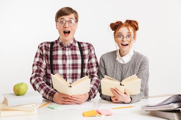 Casal engraçado de nerds escolares lendo livros