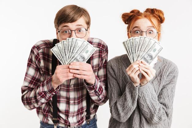 Casal engraçado de nerds escolares segurando um monte de dinheiro