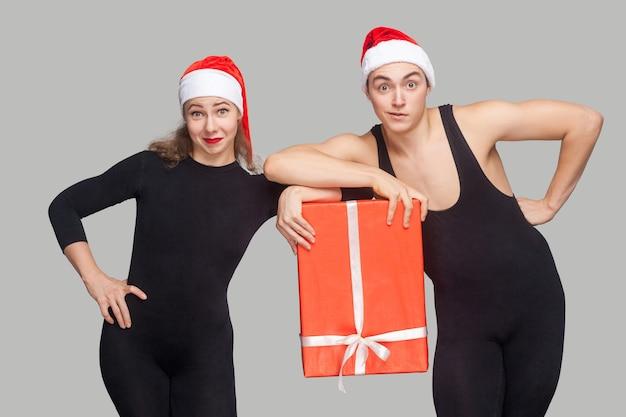 Casal engraçado em vestido preto e chapéu vermelho de natal, segurando a caixa de presente juntos e olhando para a câmera. foto em estúdio interno, isolada em fundo cinza