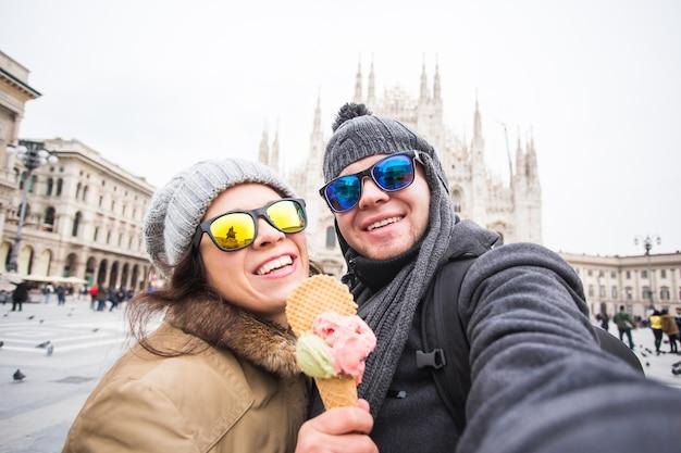 Casal engraçado tirando auto-retrato com sorvete na praça duomo.