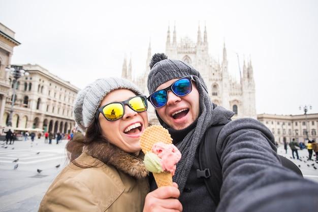 Casal engraçado tirando autorretrato com sorvete no duomo em milão
