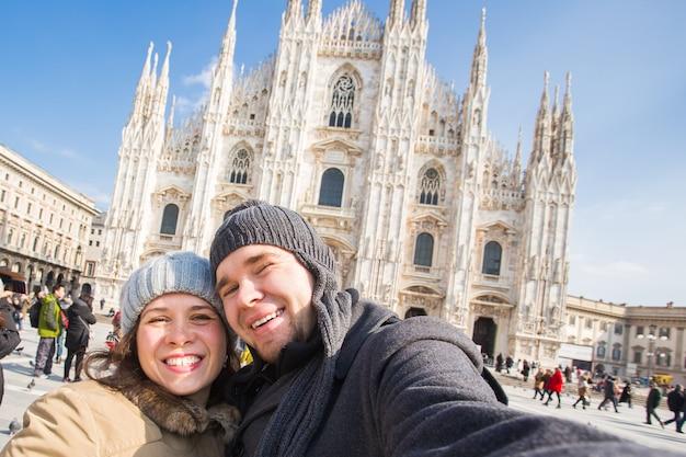Casal engraçado tirando autorretrato na praça duomo em milão, no inverno, viajando pela itália e relacionamento