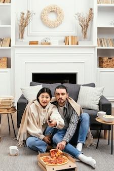 Casal enrolado em um cobertor assistindo tv e passando um tempo juntos