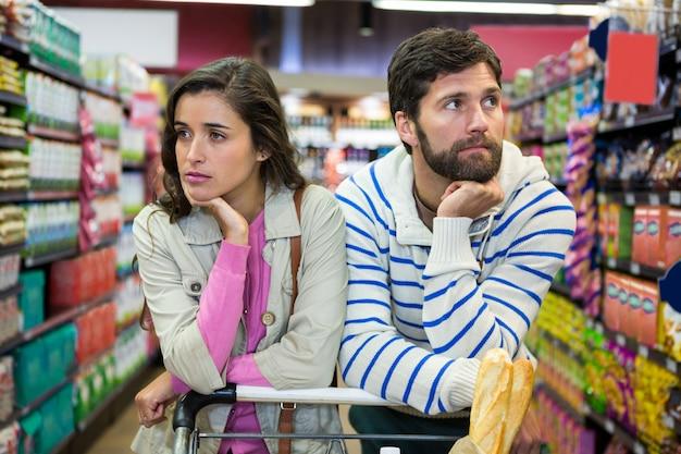 Casal entediado com carrinho de compras na seção orgânica