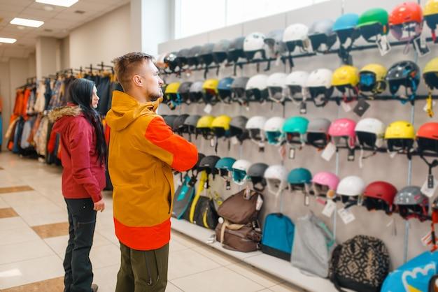 Casal escolhendo capacetes para esqui ou snowboard
