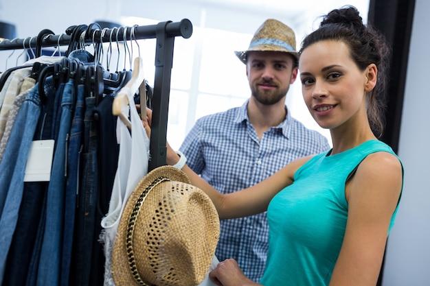 Casal escolhendo roupas de rack de roupas