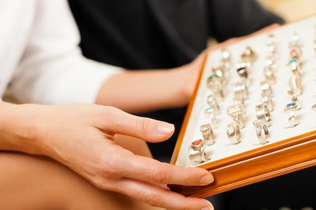Casal escolhendo um anel no joalheiro