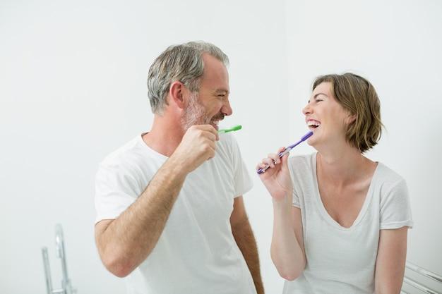 Casal escovando os dentes com escova em casa