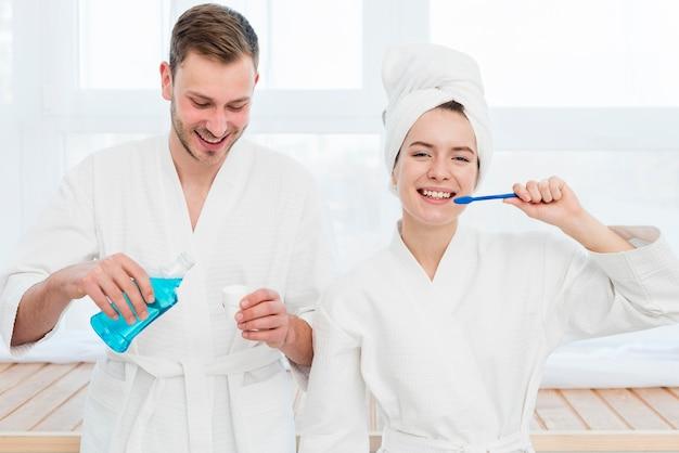 Casal escovando os dentes e usando enxaguatório bucal