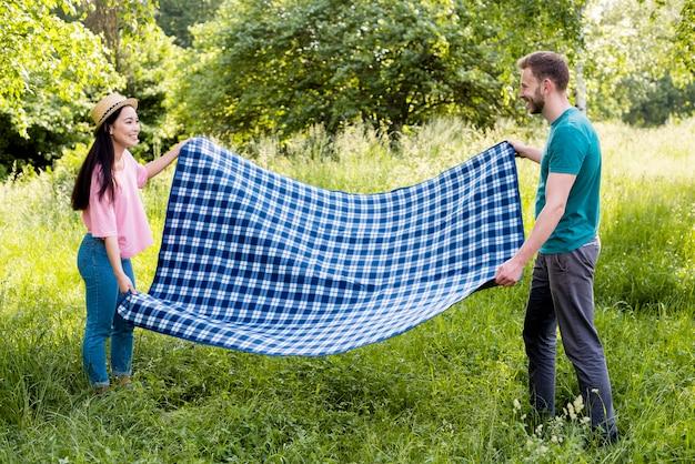 Casal espalhando cobertor para piquenique