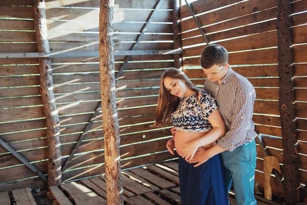 Casal esperando bebê sessão de fotos em uma casa de madeira