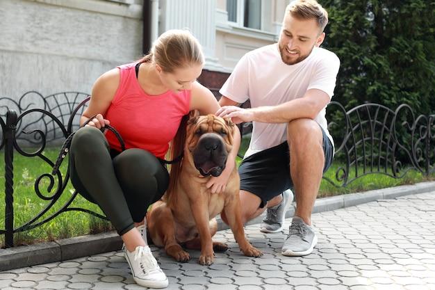 Casal esportivo com cachorro fofo caminhando ao ar livre