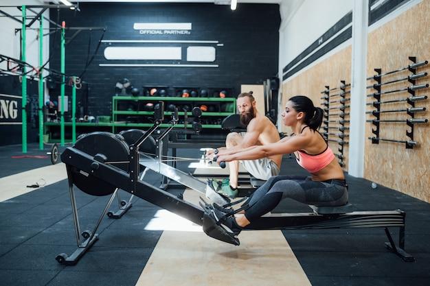 Casal esportivo cross fit treinamento remo na máquina de remador