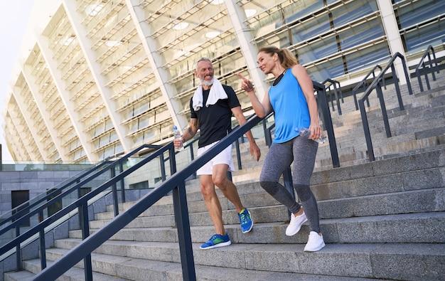 Casal esportivo de meia-idade, homem e mulher em roupas esportivas, discutindo algo enquanto caminha pela