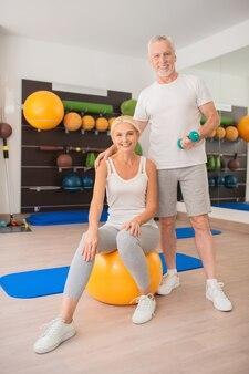 Casal esportivo em roupas esportivas se exercitando na academia