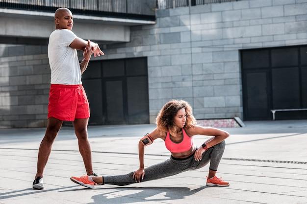 Casal esportivo. jovem simpática fazendo exercícios enquanto treina com o namorado