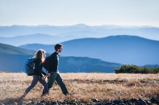 Casal está andando nas montanhas com mochilas.