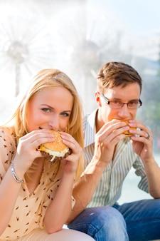 Casal está com fome e comendo um hambúrguer no intervalo