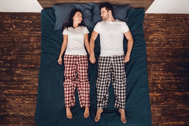 Casal está deitado na cama e de mãos dadas