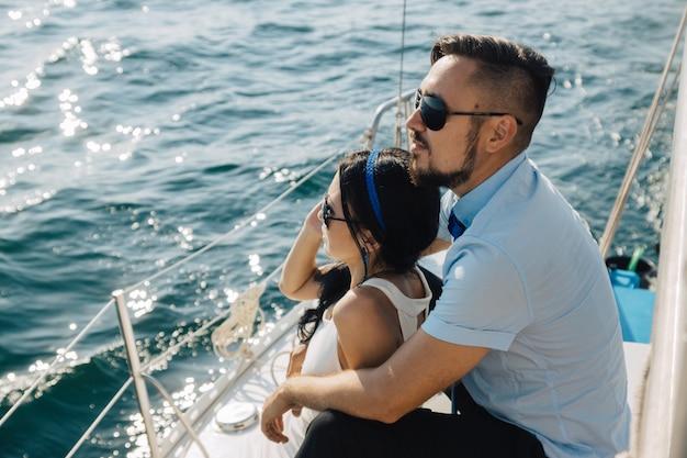 Casal está sentado no convés do iate, abraçando-se. o casal olha para o horizonte.