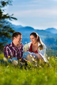 Casal está sentado no prado com montanha