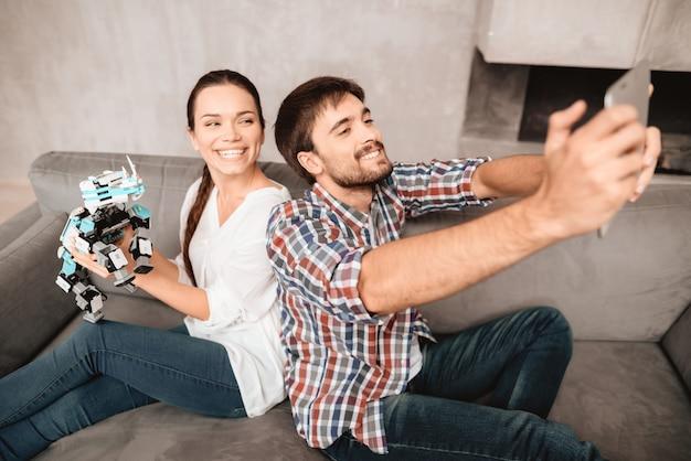 Casal está sentado no sofá e fazendo selfie com o robô.