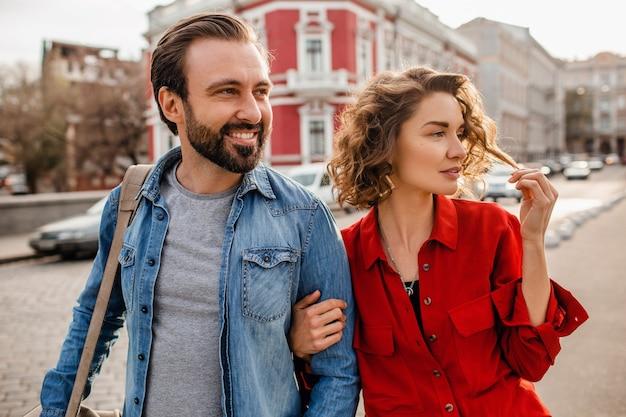 Casal estiloso apaixonado caminhando se abraçando na rua em uma viagem romântica