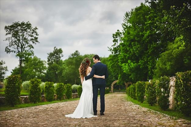 Casal estiloso de noivos caminhando juntos após a cerimônia de casamento