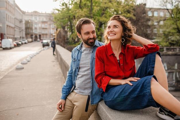 Casal estiloso e apaixonado sentado na rua em uma viagem romântica