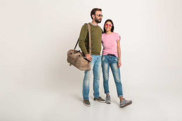 Casal estiloso isolado, mulher muito sorridente em camiseta rosa e homem de moletom segurando uma bolsa de viagem, vestido de jeans, usando óculos escuros, se divertindo juntos