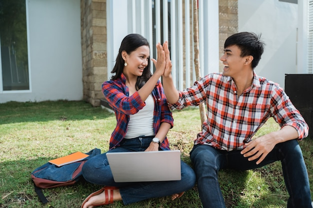 Casal estudante highfive enquanto estiver usando laptop