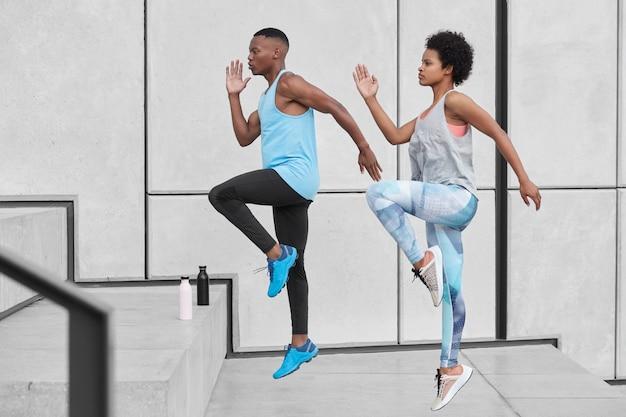 Casal étnico ativo e motivado sobe escadas correndo juntos, pula alto, treina subindo escada na cidade, usa roupas esportivas confortáveis, bebe água de garrafa, escala o desafio, escolhe o caminho difícil