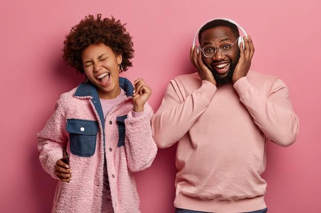 Casal étnico muito feliz tem bom humor, relaxam juntos e dançam ao som de música legal