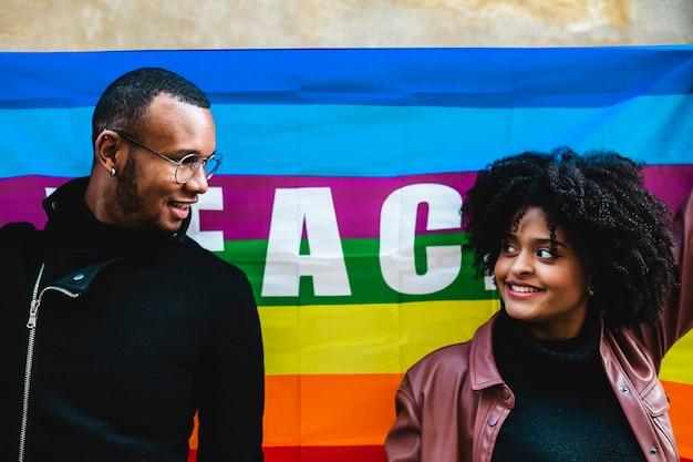 Casal étnico negro com a bandeira da paz em protesto. manifestação de liberdade sexual