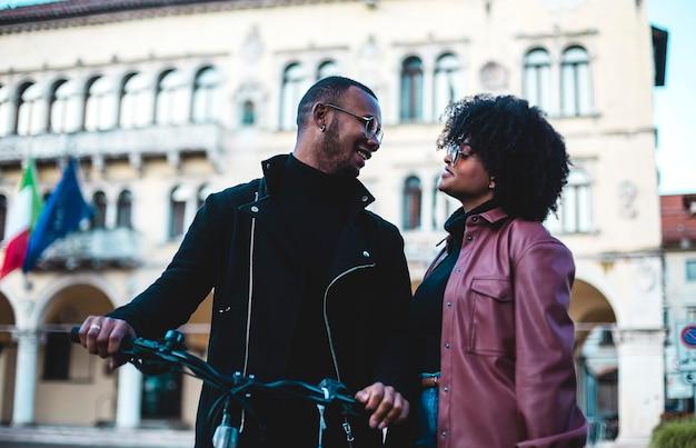 Casal étnico negro com bicicletas pelas ruas de uma cidade italiana.