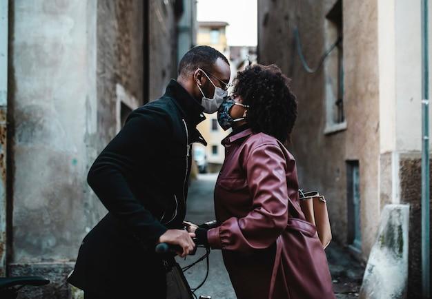Casal étnico negro com máscara protetora está se beijando.