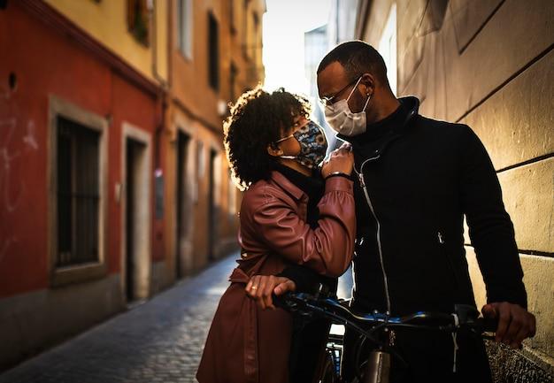 Casal étnico negro com máscara protetora se beijando ao pôr do sol de bicicleta