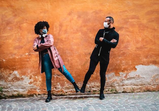 Casal étnico negro cumprimenta-se com o pé. surto de vírus, mantenha uma distância segura.