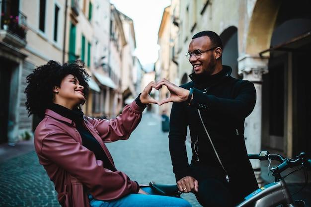Casal étnico negro se ama. jovens felizes sentados na bicicleta.