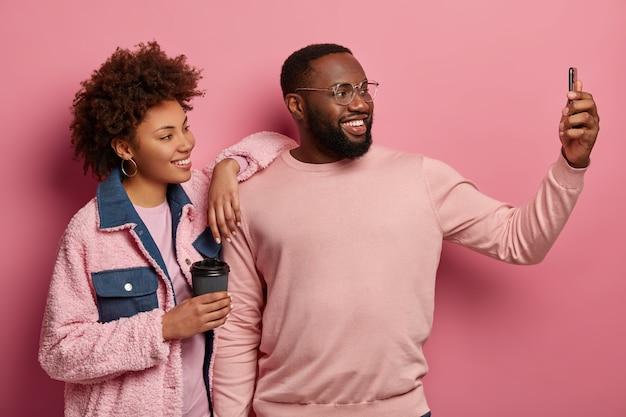 Casal étnico positivo fica próximo um do outro, faz selfie