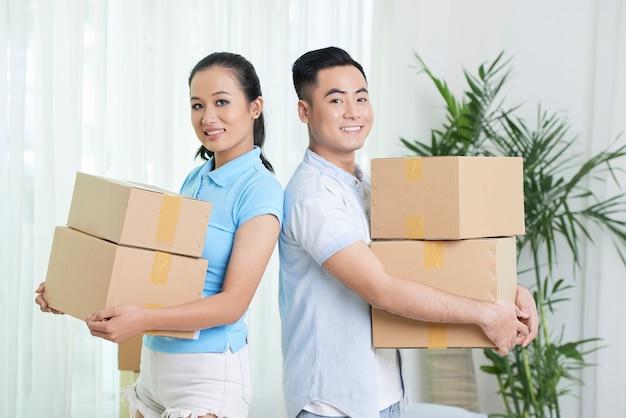 Casal étnico sorridente com caixas de papelão