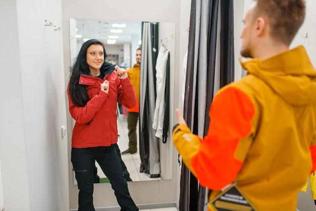 Casal experimentando jaquetas para esquiar ou praticar snowboard