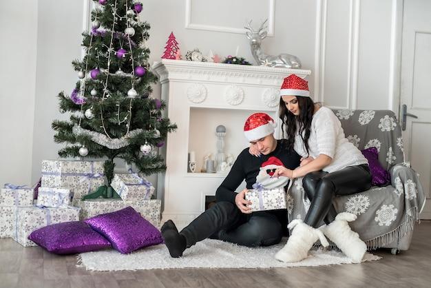 Casal familiar sentado perto da lareira com caixas de presente